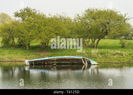 Half submerged boat wreck on the banks of a river - Stock Photo