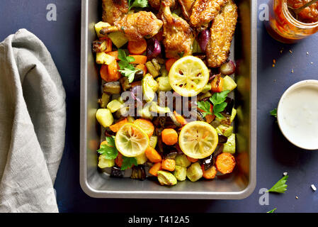 Baked vegetables and chicken wings in baking tray. Top view, flat lay - Stock Photo