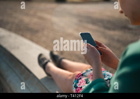 Young woman uses phone in a palace park sitting on a fountain - Close up - Stock Photo