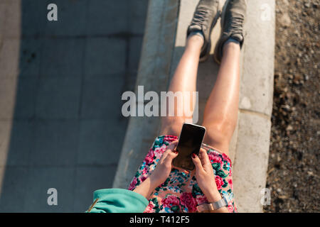 Overview of a young woman uses phone in a palace park sitting on a fountain - View from above - Stock Photo