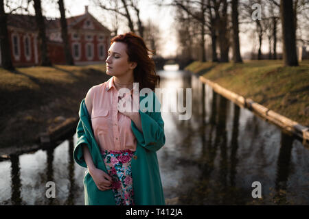 Beautiful young woman relaxing near a canal river in a park near the palace in Rundale, Latvia, 2019 - Stock Photo