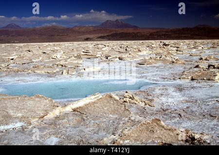 View on blue shimmering salt water puddle in rugged barren dried terrain - Salar (Salt flat) near San Pedro de Atacama - Stock Photo