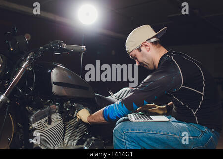 motorcycle mechanic repairing engine under supervisors guidance. video camera, laptop to view the inside of the engine to check soot. - Stock Photo