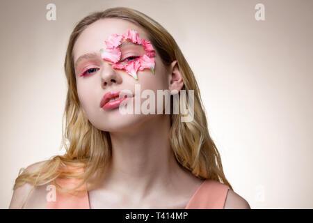 Tender blonde model having little pink petals around her eye - Stock Photo