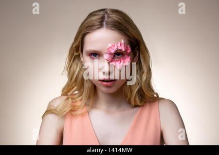 Model with pink eyeshades having flower petals around eye - Stock Photo