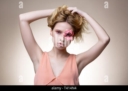 Blue-eyed model with flower petals around eye touching her hair - Stock Photo