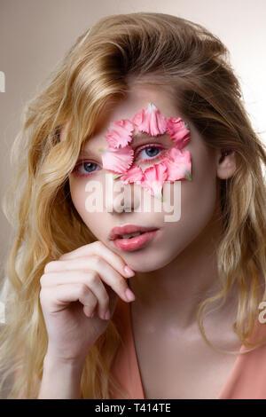 Tender blue-eyed woman having little pink petals around her eye - Stock Photo