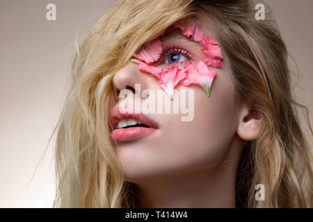 Blonde-haired model with pink lips having petals around blue eye - Stock Photo
