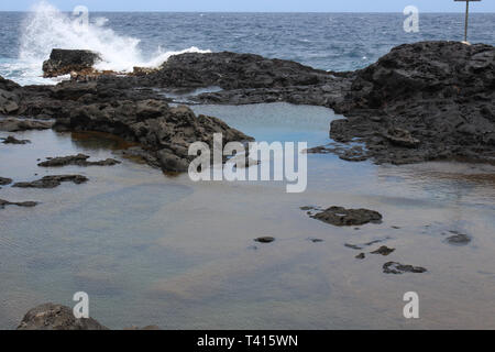 The Olivene Tide Pools on a volcanic shelf surrounded by the Pacific Ocean with waves crashing over the rocks in north Maui, Hawaii, USA - Stock Photo