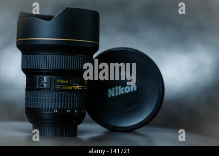 A Nikon 14-24mm wide angle zoom lens sitting against a moody grey background. - Stock Photo