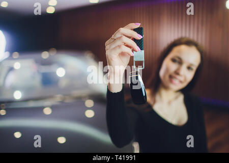 Woman Driver Holding Car Keys. Car Showroom. - Stock Photo