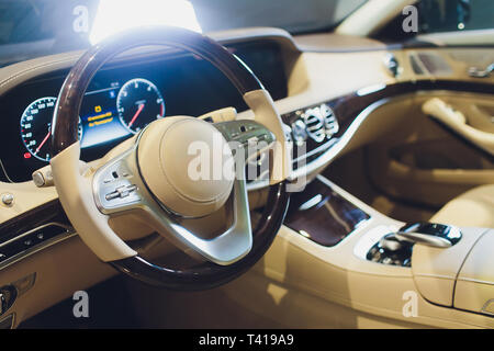 White leather interior of the luxury modern car. Leather comfortable white seats and multimedia. Steering wheel and dashboard. Automatic gear stick - Stock Photo