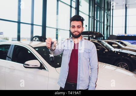 Happy buyer holding keys near the car in front of the modern avtosalon building. - Stock Photo