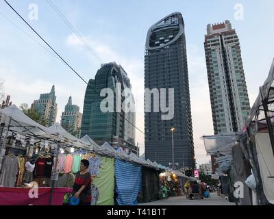 BANGKOK, THAILAND - APRIL 16, 2018: Old one story market meets huge skyscrapers - Concrete jungle - Stock Photo
