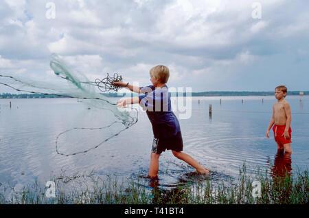 Alabama Gulf Coast Gulf Shores Gulf State Park Lake Shelby boys cast fishing net - Stock Photo