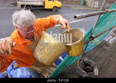 Builder on a lader holding buckets in hand, Caerleon, South Wales 19/10/2004 - Stock Photo
