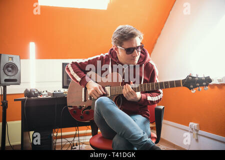 A musician man playing guitar in the studio - Stock Photo