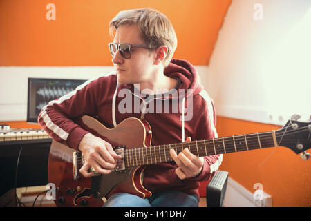 A musician man in glasses playing guitar and recording the sound in the studio - Stock Photo