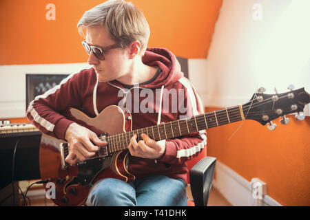 A musician man in glasses playing guitar and recording a song in the studio - Stock Photo