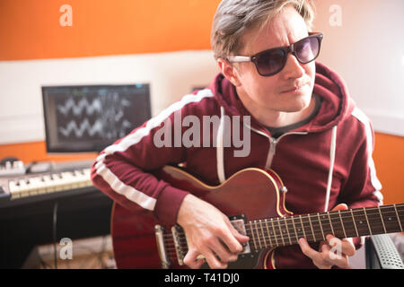 A man in glasses playing guitar and recording a song in the studio - Stock Photo