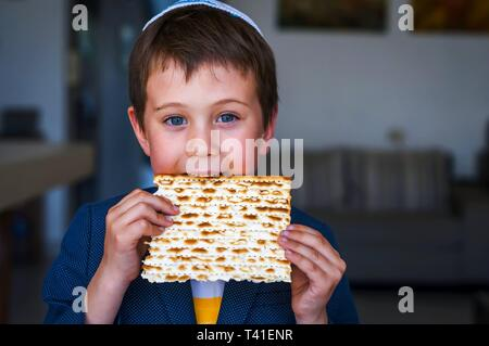 Cute Caucasian Jewish boy holding in his hands and taking a bite from a traditional Jewish matzo unleavened bread. Jewish Passover Pesach concept - Stock Photo