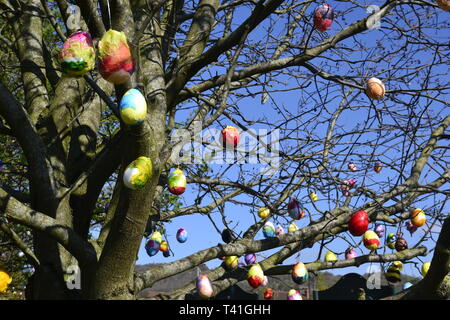 Deocrated eggs on trees in Princes Risborough, Buckinghamshire, UK. Created by local children, to celebrate the Easter Weekend 2019 - Stock Photo