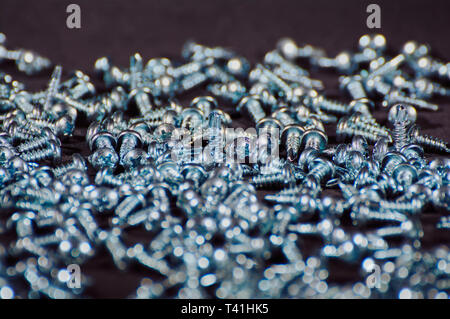 self-tapping screws on black background close up - Stock Photo
