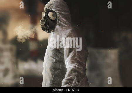 survivor with white overall and gas mask in front of blurred incineration plant and apocalyptic environment - Stock Photo