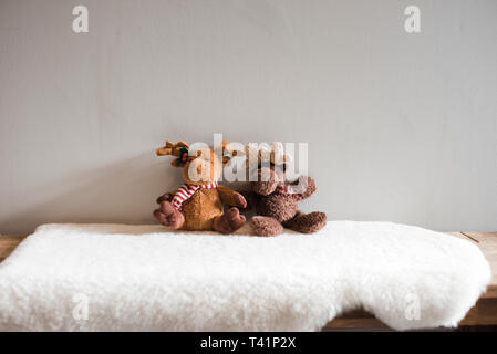 Two moose children's soft toys sitting on a white rug - Stock Photo