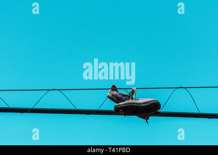 2019, January. Florianopolis, Brazil. Sport tennis shoes tied on the electric wire against a clear blue sky. - Stock Photo