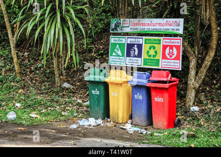 This unique photo shows garbage separation in Thailand. you put on trash cans but people throw the plastic waste anyway in the nature - Stock Photo