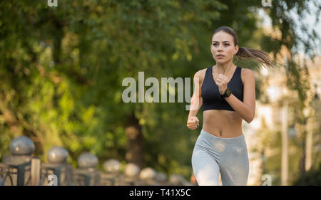 Motivated millennial woman running forward to goal - Stock Photo
