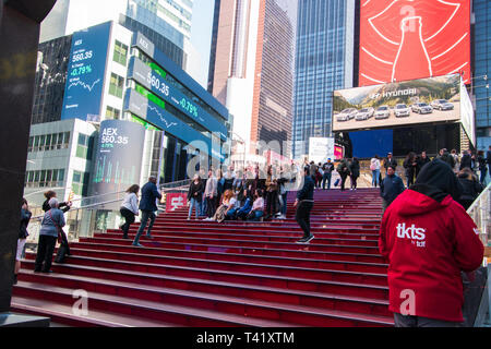 New York, NY - April 3, 2019: Large group of young students gather on the bleachers in Times Square Manhattan, New York to take a picture - Stock Photo