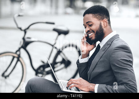 African-american businessman using laptop, having break outdoors