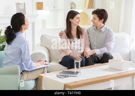 Happy couple at successful therapy session with family psychologist - Stock Photo