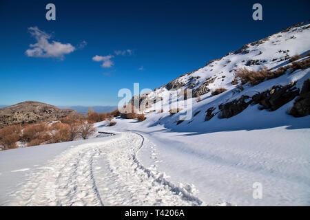 The road from Anogeia village to Nida plateau covered with snow. Psiloritis mountain, Rethimno, Crete, Greece. - Stock Photo
