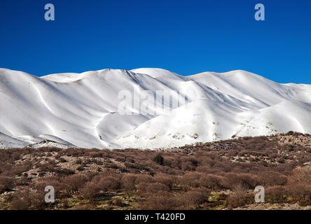 The highest peaks of Psiloritis mountain as seen from the Anogeia - Nida plateau road. Rethymno, Crete, Greece. - Stock Photo