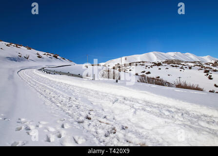 The road to Nida plateau covered with snow. In the background the highest peaks of Psiloritis mountain. Rethimno, Crete, Greece. - Stock Photo