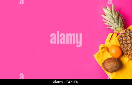 Composition of various fresh exotic fruits with a pink cotton bag on a pink background. Flat lay. Food concept. - Stock Photo