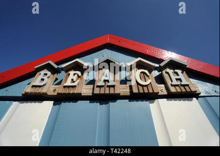 BEACH HUT WITH 'BEACH' SIGN AND BLUE SKY RE HOLIDAYS SUNSHINE WEATHER RELAXING ETC UK - Stock Photo
