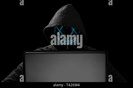hacker with glowing mask behind notebook laptop in front of isolated black background internet cyber hack attack computer concept - Stock Photo