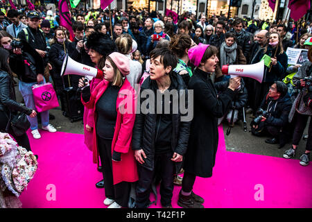 London, Londo, UK. 12th Apr, 2019. Activists are singing during the event.The Extinction Rebellion Fashion Action group went to Oxford Circus to a standstill by staging a creative and symbolic catwalk titled Fashion: Circus of Excess. The objective is to raise the alarm about the role fashion consumption plays in fuelling the Climate and Ecological emergency. The fashion industry is set to consume a quarter of the world's carbon budget by 2050 in clothing production. Credit: Brais G. Rouco/SOPA Images/ZUMA Wire/Alamy Live News - Stock Photo