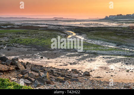 Northam Burrows, Devon, UK. Saturday 13th April 2019. UK Weather - After a very cold night in the South West of England, dawn brings a colourful sunrise over the mudflats at Northam Burrows near Appledore in North Devon. Credit: Terry Mathews/Alamy Live News - Stock Photo