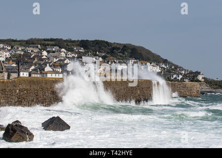 Mousehole, Cornwall, UK. 13th Apr, 2019. UK Weather. Winds of 50mph, and big waves batter the harbour wall at Mousehole this lunchtime. Despite the wind it was still sunny. Credit: Simon Maycock/Alamy Live News - Stock Photo