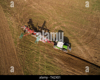 aerial view  of modern tractor working on the agricultural field - tractor plowing and sowing in the agricultural field