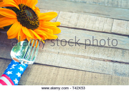 Fourth of July Picnic or BBQ Table Place Setting with Red, White, and Blue, stars and stripes napkin around fork and knife with sunflower on Rustic Wo - Stock Photo