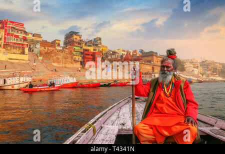 Sadhu baba sitting on a wooden overlooking ancient Varanasi city architecture with Ganges river ghat at sunset. - Stock Photo