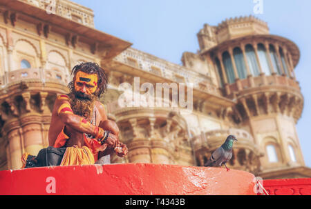 Sadhu baba sitting at Varanasi Ganges ghat with ancient architecture building as the backdrop. - Stock Photo