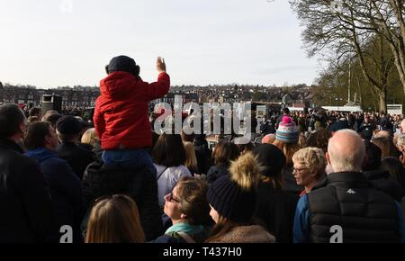 A boy waves during the Mi Amigo 75th anniversary memorial flyover event at Endcliffe Park in Sheffield, England, Feb. 22, 2019. Thousands of people gathered and watched a flyover in remembrance of the Mi Amigo crew who crashed and perished during World War II. - Stock Photo