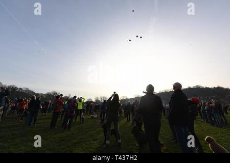 Audiences take photos and watch the Mi Amigo 75th anniversary memorial flyover at Endcliffe Park in Sheffield, England, Feb. 22, 2019. 48th Fighter Wing F-15E Strike Eagles demonstrated a missing man formation to pay tribute to the Mi Amigo crew who gave the ultimate sacrifice during World War II. - Stock Photo